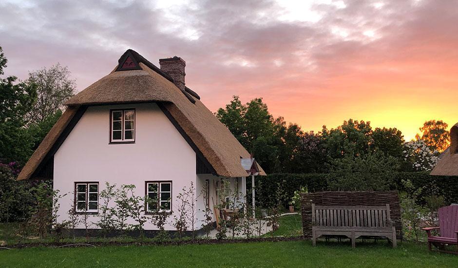 Das Brunnenhaus der Hoheneichen Hohwacht Reetdach Ferienhäuser in der Abendstimmung
